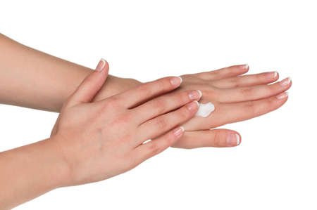 Woman hands with french manicure applying hand cream isolated on white background photo