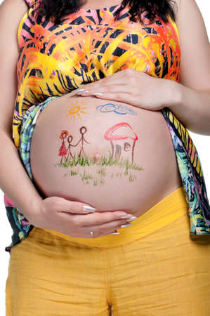 Tummy of pregnant woman with funny drawing over white background photo