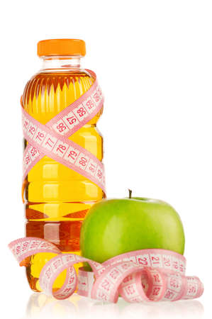 Apple juice in plastic bottle with a measure tape isolated on white background photo