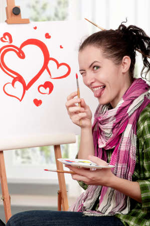 Love or Valentine day - concept image  Beautiful girl with brushes near easel, painting on canvas   photo