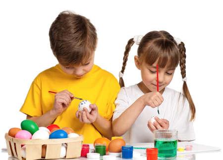enfants peinture: Deux enfants de peinture des oeufs de P�ques isol� sur fond blanc