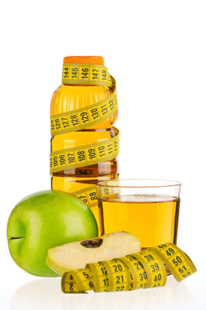 Apple juice in plastic bottle and glass with a measure tape isolated on white background Stock Photo - 12696586