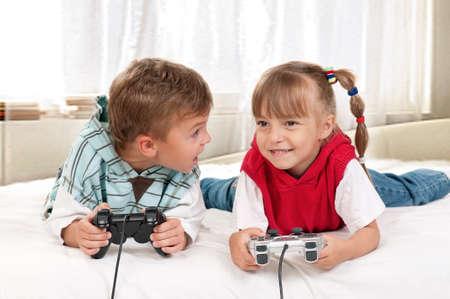 niños jugando videojuegos: - Los niños felices de chico y chica jugando con un videojuego