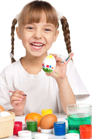 Pretty little girl painting Easter eggs isolated on white background - focus on egg photo