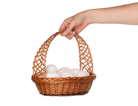 Basket with eggs in woman hand isolated on white background photo