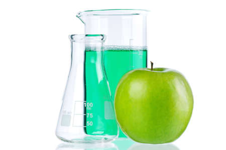 Genetically modified organism - ripe apple with laboratory glassware on white background photo