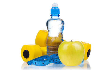 Yellow one kilogram dumbbells with apple, bottled water and measuring tape isolated on white background photo