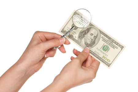 Woman hands with magnifying glass and dollars isolated on white background photo