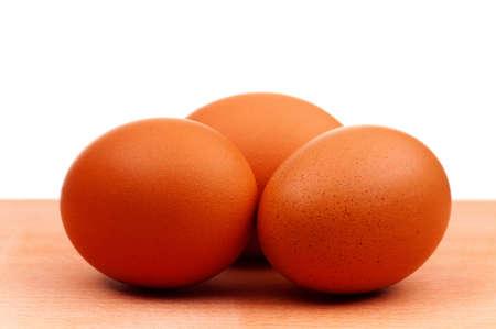 Fresh chicken eggs on wooden board over white background photo