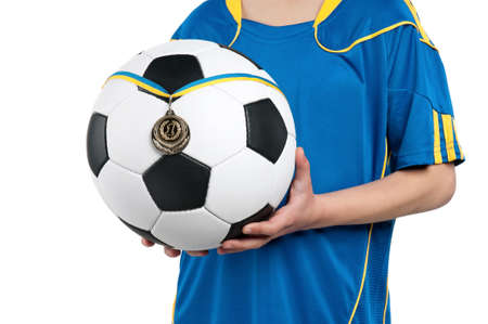 Little boy in ukrainian national soccer uniform with classic soccer ball and medal on isolated white background photo
