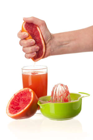 Glass of fresh grapefruit juice, juicer and hand with half of grapefruit on white background Stock Photo - 13103868