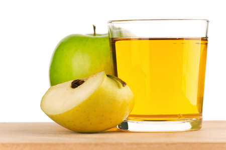Apple juice in glass on wooden board over white background photo