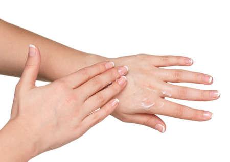 partes del cuerpo humano: Manos de mujer con manicure francés de aplicar la crema a mano sobre fondo blanco