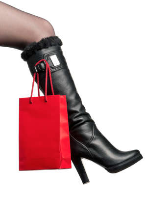 foot gear: Detail of standing woman wearing fashionable black boots posing on white