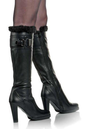 Detail of standing woman wearing fashionable black boots posing on white photo