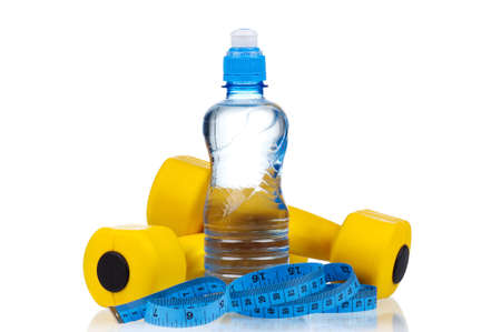 Yellow one kilogram dumbbells with bottled water and measuring tape isolated on white background photo