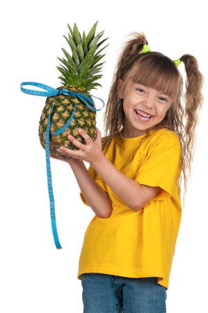 Portrait of little girl with pineapple and blue measure over white background photo