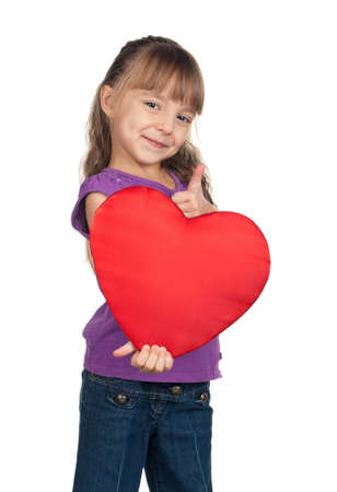 Portrait of little girl holding red heart and giving you thumb up over white background photo