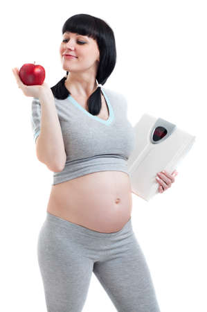 Pregnant woman with red apple and weight scales on a white background photo