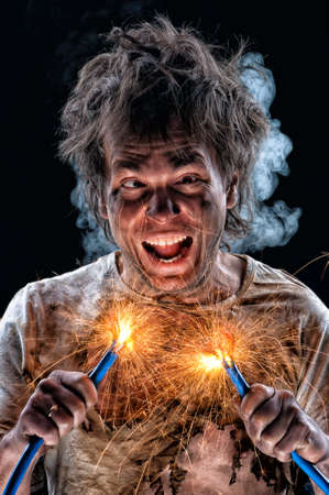 electric spark: Portrait of crazy electrician over black background Stock Photo
