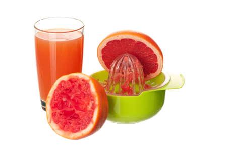 Glass of fresh grapefruit juice, juicer and grapefruit fruits on white background photo