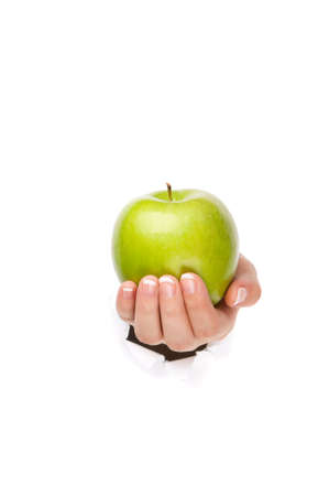 Woman hand with green apple through a hole in paper isolated on white background photo