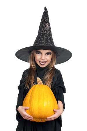 Portrait of little girl in black hat and black clothing with pumpkin on white background photo