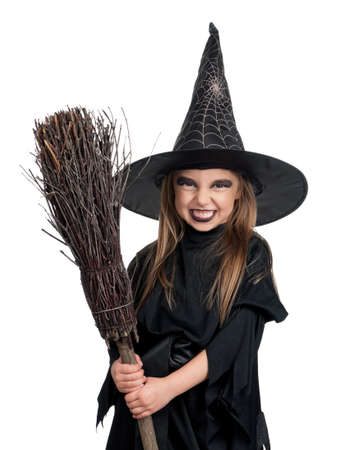 Portrait of little girl in black hat and black clothing with broom on white background photo