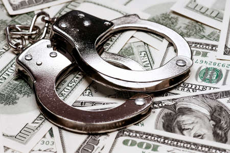 Handcuffs on money background as security concept photo