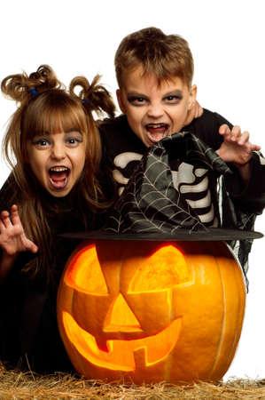 calabazas de halloween: Chico y chica con disfraz de Halloween con calabaza sobre fondo blanco Foto de archivo