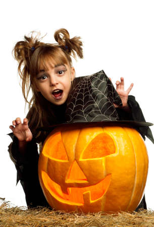 Portrait of little girl in black clothing with pumpkin on white background photo