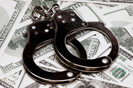 wristlets: Handcuffs on money background as security concept Stock Photo