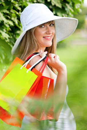 Young pregnant woman holding shopping bags - outdoors photo
