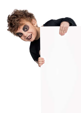 Portrait of little boy wearing halloween costume with empty white board on white background photo