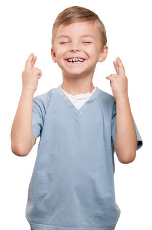 Portrait of superstitious little boywith crossed fingers over white background photo