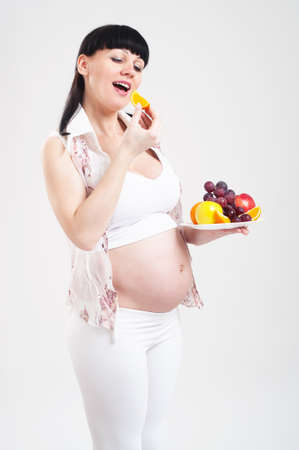 plateful: Pregnant woman with a plateful of fruit on a grey background Stock Photo