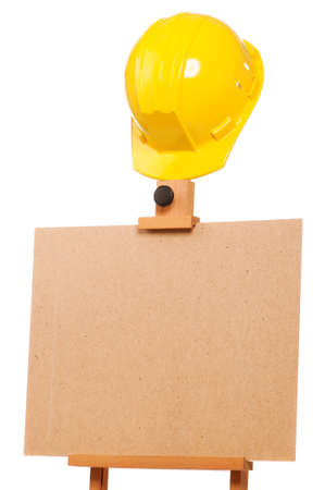 Wooden easel with hard hat isolated on white background photo