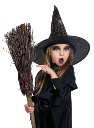 brooms: Portrait of little girl in black hat and black clothing with broom on white background Stock Photo
