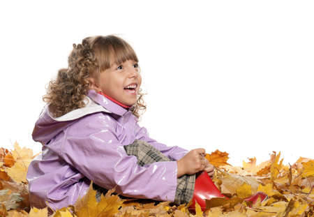 Portrait of a little girl with yellow foliage posing on white background photo