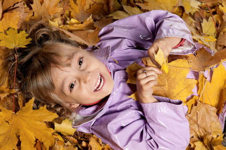 Portrait of a little girl with yellow foliage posing on white background Stock Photo - 15287473