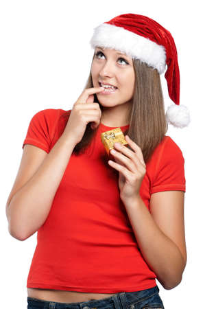 Beautiful teen girl in Santa hat with gift box posing on white background photo
