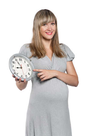 Happy pregnant woman with clock isolated on white background photo