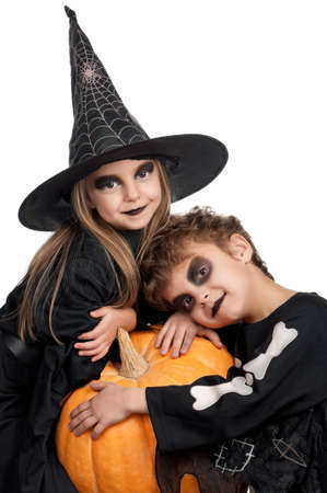 Boy and girl wearing halloween costume with pumpkin on white background photo