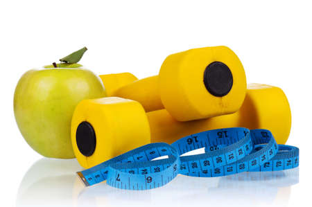 kilogram: Yellow one kilogram dumbbells with apple and measuring tape isolated on white background