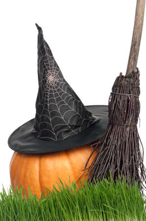 Halloween pumpkin with black hat and broom isolated on white background photo