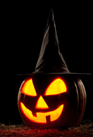 Funny Halloween pumpkin with black hat isolated on black background photo