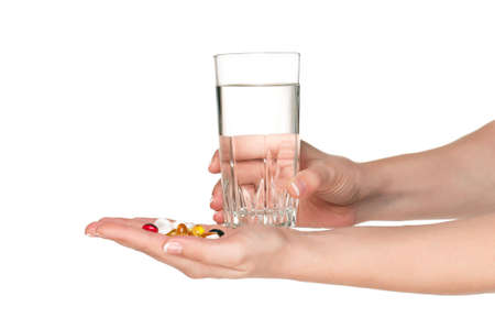 Woman hands with pills and glass of water isolated on white background Stock Photo - 15334428