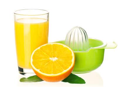 Glass of fresh orange juice, juicer and orange fruits with green leaves on white background