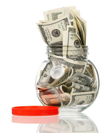 Many dollars in a glass jar isolated on white background Stock Photo