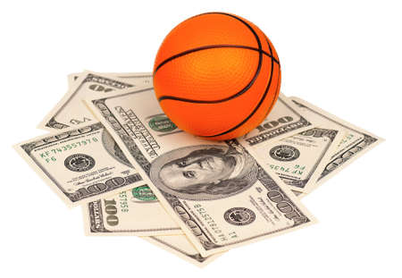 Small basketball ball on heap of dollars isolated on a white background photo
